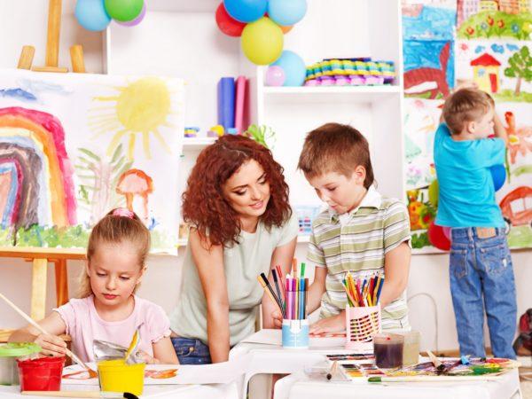 Дети рисуют, педагог помогает