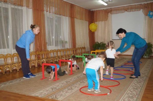 Воспитатели помогают детям пройти по препятствиям из хулахупов и планок