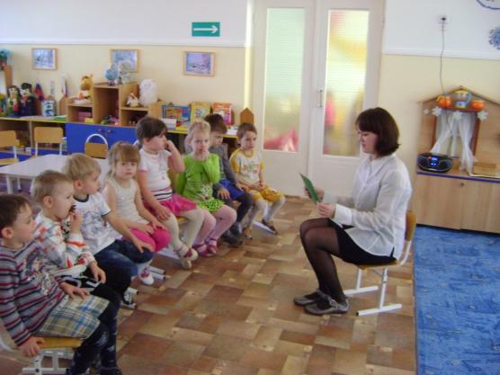 Воспитательница и сидящие полукругом дети