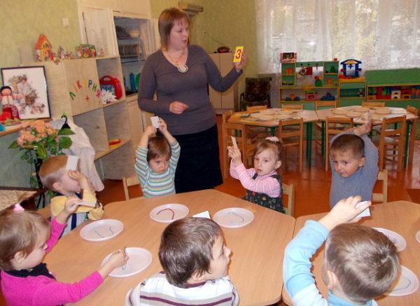 Воспитательница показывает детям цифру три