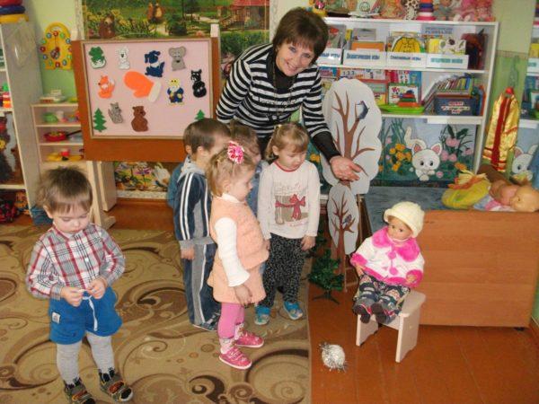Воспитательница показывает детям куклу, сидящую на стуле