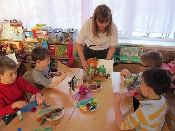 Воспитательница с игрушкой в руке объясняет детям задание