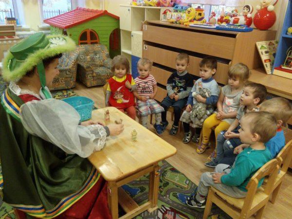 Воспитательница в костюме показывает детям маленьких кукол