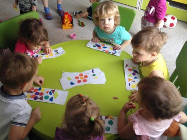 Дети, сидя за столом, составляют узоры на бумаге из разноцветных геометрических фигур