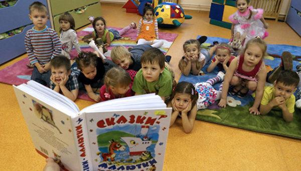 Дети лежат на ковре и рассматривают книгу