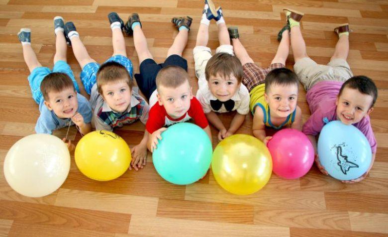 Дети лежат на полу с воздушными шариками