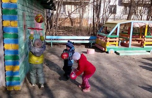 Дети на улице забрасывают мячи в баскетбольную корзину
