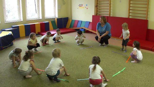 Дети присели с лентами вместе с педагогом