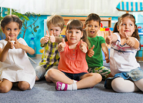 Дети сидят на коврике и показывают большой палец