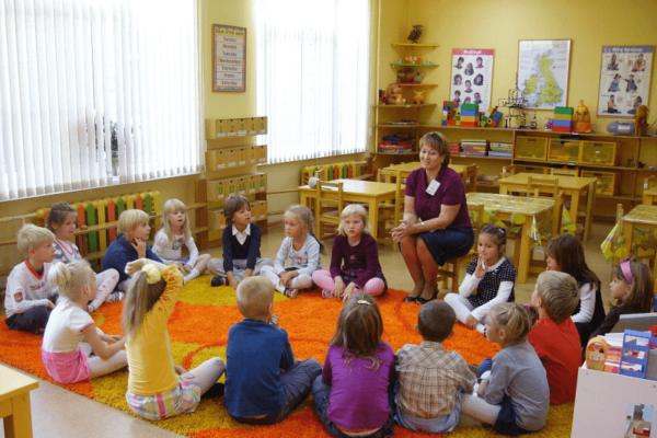 Дети сидят на оранжевом коврике вокруг воспитателя