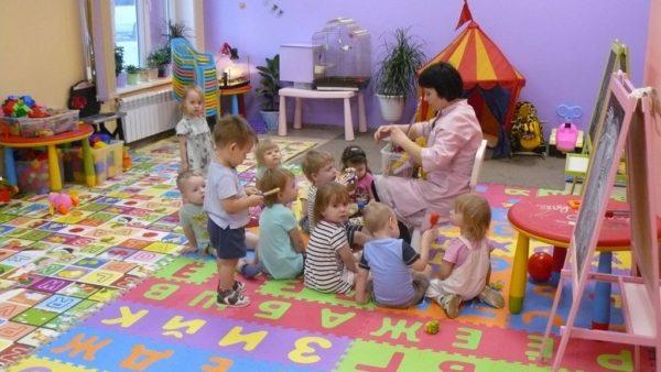 Дети сидят вокруг педагога с коробкой с игрушками