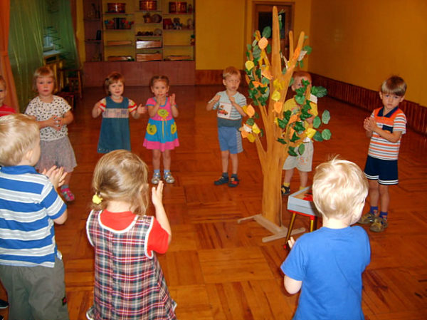 Дети стоят вокруг декорации дерева с осенними листьями