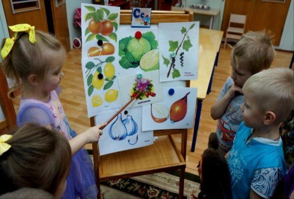 Девочка показывает указкой на картинки с фруктами и овощами
