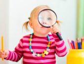 Девочка с карандашом в руках смотрит через лупу
