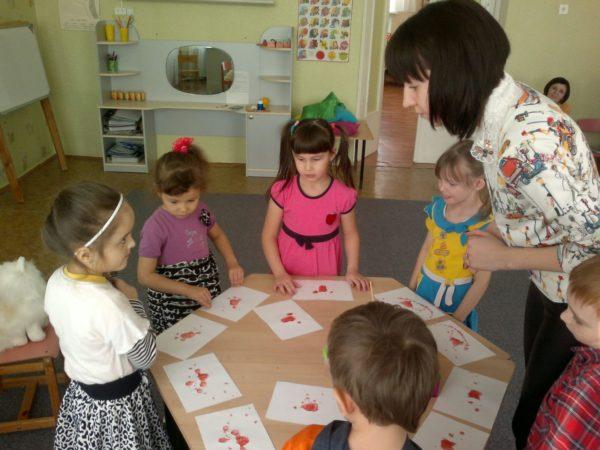 Дети и педагог разглядывают листы бумаги с кляксами