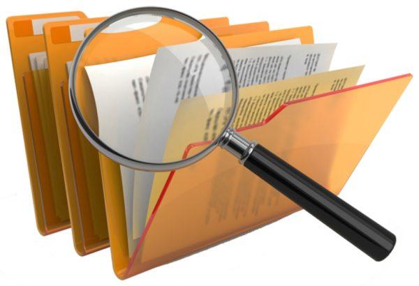 Лупа и папки с документами