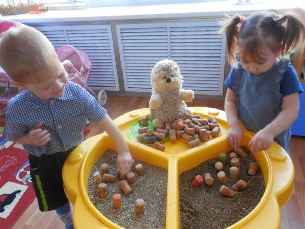 Мальчик и девочка играют с песком и древянными фигурками
