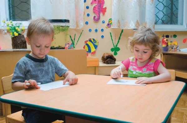 Мальчик и девочка выполняют задание, сидя за столом