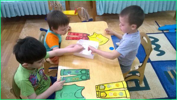 Мальчики раскладывают элементы декора на бумажные брюки
