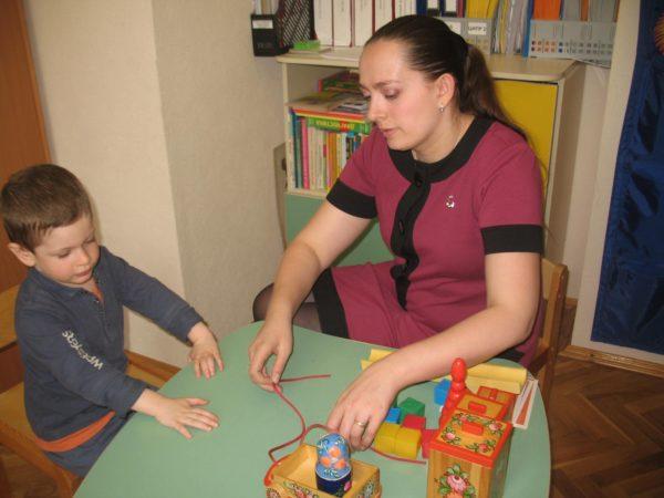 Педагог и ребенок играют со шнуровкой