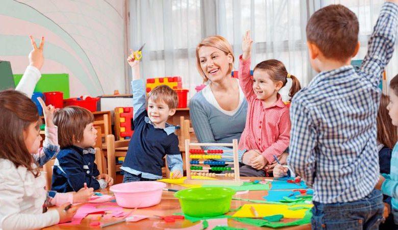 Педагог и дети, выполняющие аппликацию