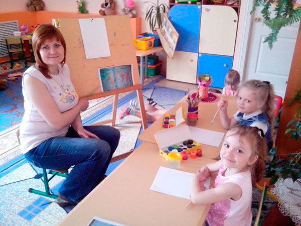 Педагог и три девочки за столом