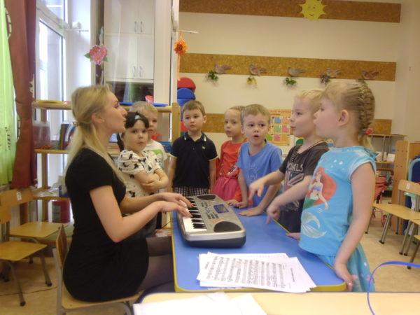 Педагог играет детям на электронном пианино