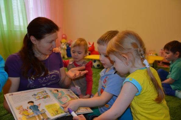 Педагог показывает детям открытую книгу