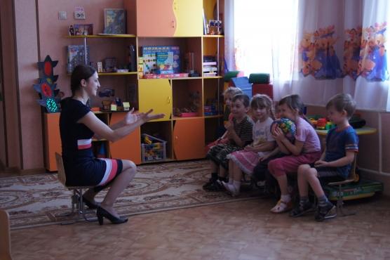 Педагог показывает упражнение сидящим напротив детям
