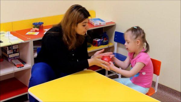Педагог работает с девочкой с синдромом Дауна