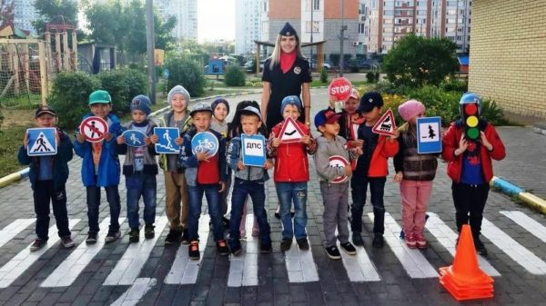 Дети стоят на пешеходном переходе со знаками ПДД в руках