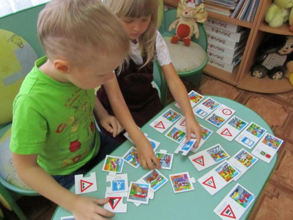 Две детей складывают карточки со знаками ПДД