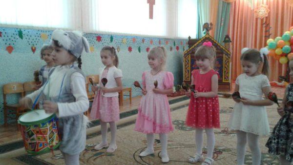 Дети на утреннике, мальчик в костюме зайца играет на барабане
