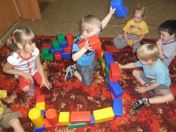 Дети играют на ковре с пластиковыми строительными модулями