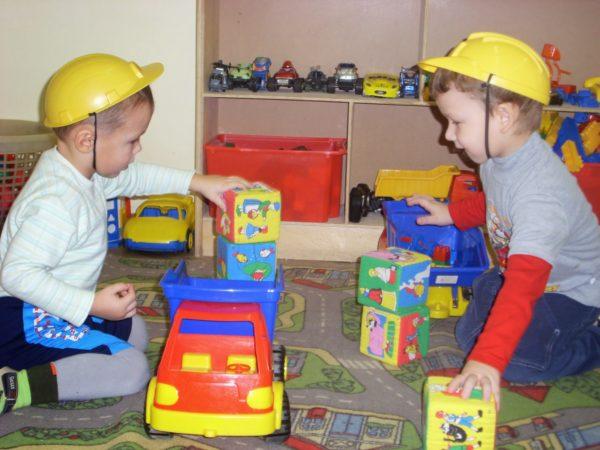 Два мальчика в строительных касках играют с кубиками и машинками