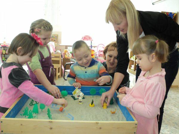 Дети и психолог занимаются песочной терапией