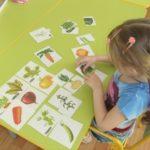 Девочка собирает разрезные картинки «Овощи» - соединяет вершки и корешки