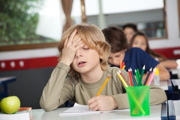Мальчик на уроке закрыл глаза и подпёр голову рукой
