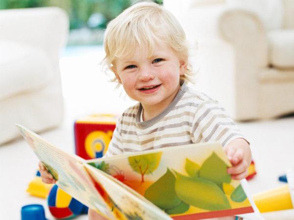 Дошкольник 3–4 лет изучает книгу с картинками