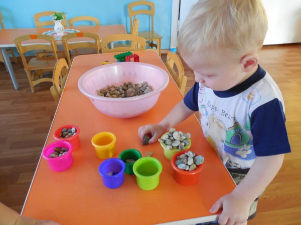 Дошкольник раскладывает камешки по баночкам