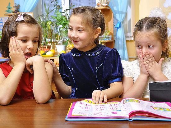 Три девочки рассматривают книгу