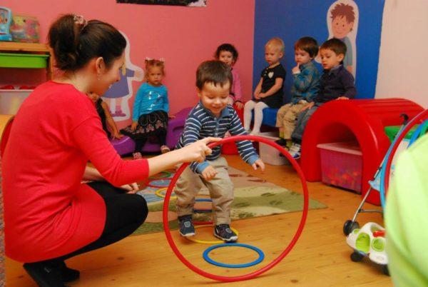 Воспитатель держит обруч, малыш проходит через него