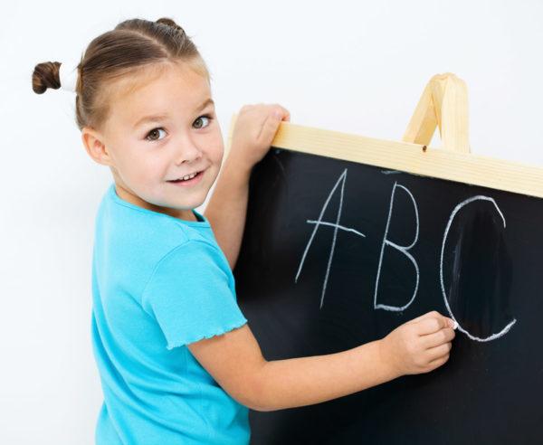 Девочка пишет английский алфавит мелом на доске