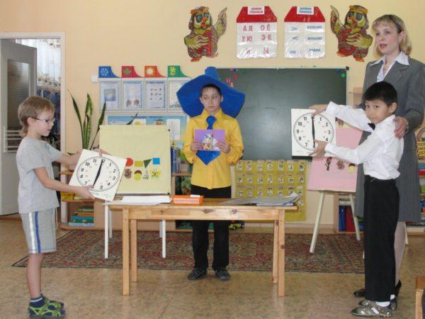 Ребёнок в костюме Незнайки, два мальчика с картонными часами в руках и педагог
