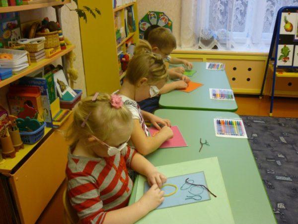Слабовидящие дети выполняют упражнение за столиками