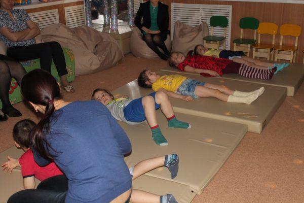 Педагог помогает детям выполнять упражнения лёжа