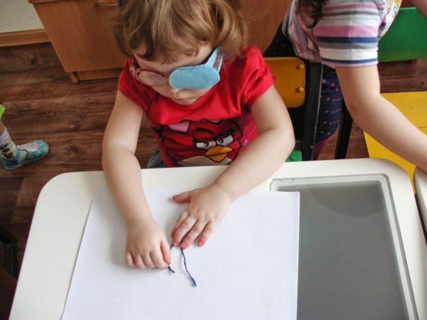 Девочка выкладывает рисунок ниткой