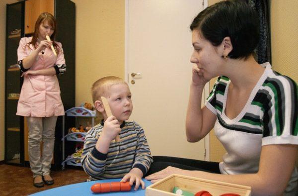 Мальчик и педагоги занимаются улучшением слуха