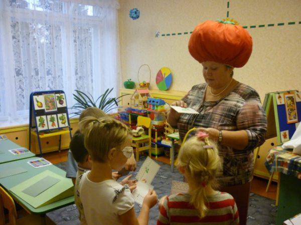 Педагог с тыквой на голове раздаёт детям карточки