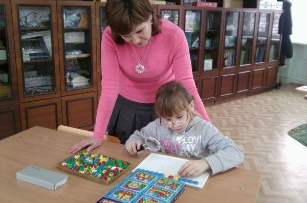 Педагог наблюдает, как девочка выкладывает мозаику